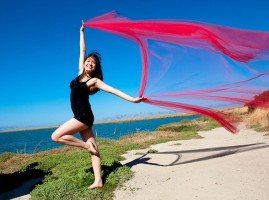 [image] A dancer stands on a beach, posing on one leg with a long scarf extended in the breeze. [image]
