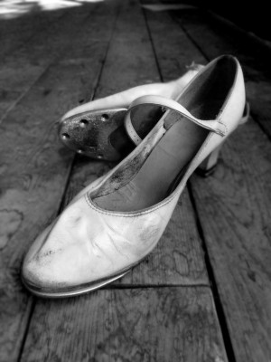 IMAGE Black and white photo of a well-worn pair of women's character tap shoes. IMAGE