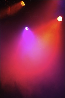 IMAGE Colorful spotlights illuminate a foggy stage. IMAGE