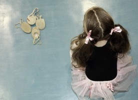 IMAGE A young ballerina sits on a blue floor near a group of ballet slippers IMAGE