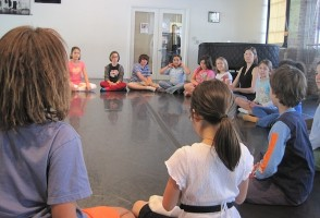 [image] Children sit in a circle at Hope Center's dance studio [image]