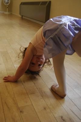 Photo of a little dancer posing upside-down
