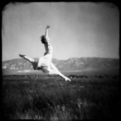 Dancer frolicking in the grass with a mountain in the background
