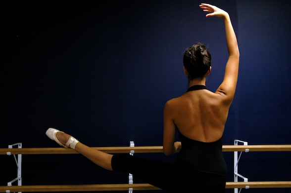 Photo of a dancer from the back, stretching at the barre