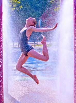Photo of a dancer splashing through a spray park water fountain