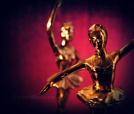 Two dance trophies against a deep pink backdrop