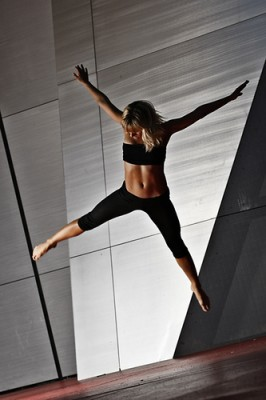 A dancer seems to hover in mid-air, forming an X shape against a geometric background.