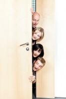 Four parents peek around the door into a studio