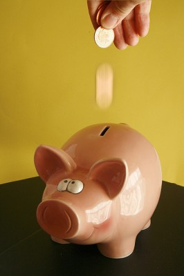 A photo of someone dropping coins into a piggy bank