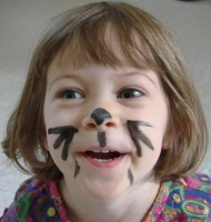 A little girl with black whiskers and a cat's nose painted on her face.