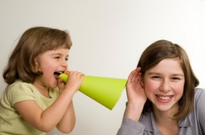 A little girl uses a megaphone to tell a secret to another