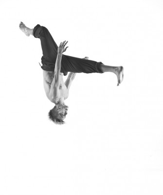 A black and white photo capture of a male dancer mid-flip, upside-down