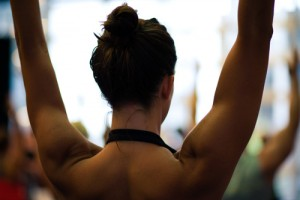 A young woman's arms, head, neck and shoulders are shown as she reaches overhead in a fitness class