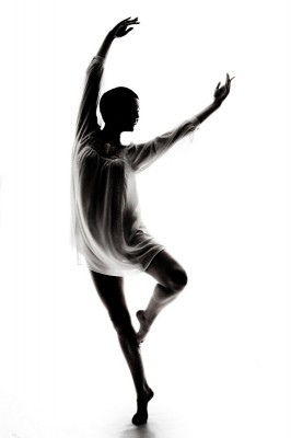 A dancer, her face and form eclipsed by shadow, arcs her body