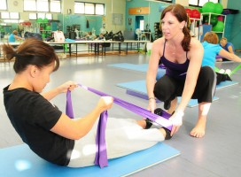 An instructor helps a student strengthen with an elastic resistance band