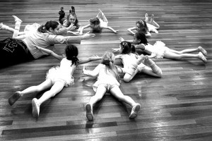 IMAGE Young dancers lying on their tummies in a circle with their teacher. IMAGE