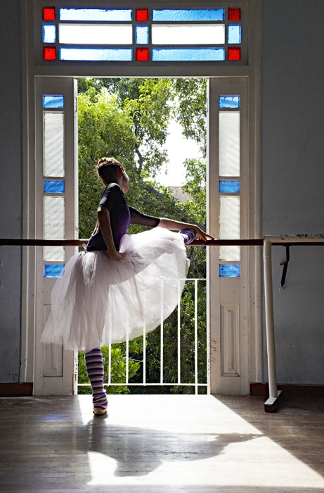 IMAGE Dancer Grettel Morejon of Ballet Nacional de Cuba stretches at the barre. Light streams through her skirt as she stands before a sunlit window. IMAGE