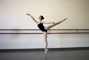 IMAGE A ballet dancer in leotard and tights poses in arabesque inside a dance studio. IMAGE