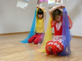 IMAGE Two girls in a dance class site and hold scarves over their heads IMAGE