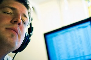IMAGE A man listens to music through headphones with his eyes closed. A computer screen is in the background. IMAGE