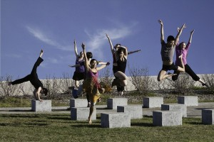 IMAGE A group of dancers jump into the air over concrete blocks. IMAGE