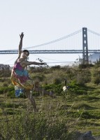 IMAGE A lone dancer in a colorful dress dances in a field with San Fancisco's Golden Gate Bridge in the background. IMAGE