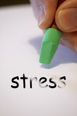 IMAGE A person uses a green pencil eraser to rub out the word stress. IMAGE