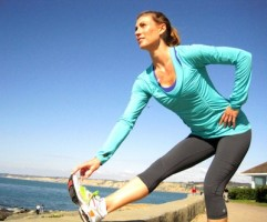 IMAGE A woman stretches her hamstring with one leg up on a low wall by the sea. IMAGE