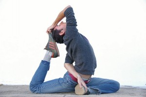 IMAGE An example of a Pigeon pose in Yoga by someone in jeans, a hoodie, and sneakers. IMAGE