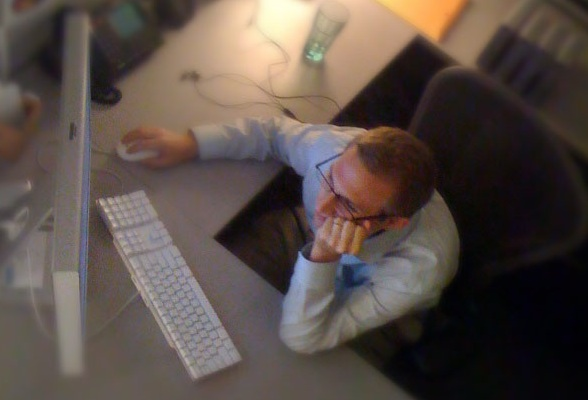 IMAGE Birdseye view of a man slouching at his office computer desk. IMAGE