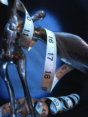 IMAGE Measuring tape winds around a statue of a figure bending sideways like a dancer. IMAGE