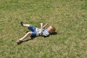IMAGE Child rolling in the grass. IMAGE