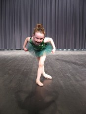 IMAGE A young dancer in a green tutu does a curtsey-style bow toward the camera. IMAGE