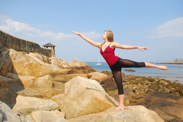 IMAGE Staring at the Sea by Kristen Newsom - a dancer stands in arabesque on a rocky New England coastline. IMAGE
