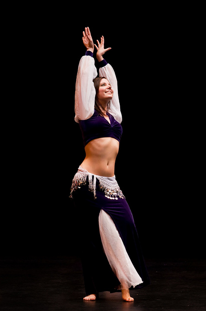 IMAGE A belly dancer poses with arms above her head, a confident smile on her face. IMAGE