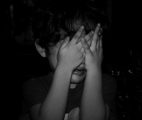 IMAGE A child covers his eyes, crying IMAGE