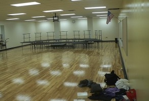 IMAGE A large hardwood covered space with risers at one end and backpacks at the other. IMAGE