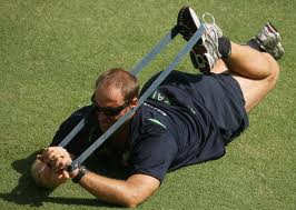 IMAGE A man lies on the ground, knee bent, exercising with a resistance band IMAGE