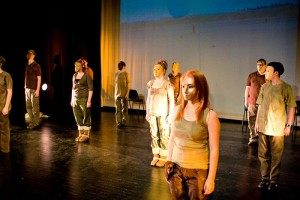 IMAGE Students stand on a lit stage space wearing theatrical gold masks IMAGE