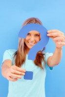 IMAGE A girl in a blue shirt holds a blue question mark. IMAGE
