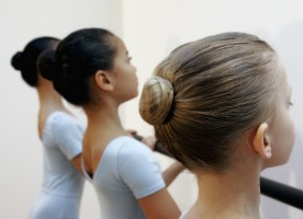Three young dancers stand at the barre, their tiny hair buns perfectly poised on their heads.