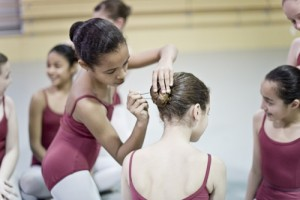 A young dancer in leotard and tights bobby pins her classmate's bun in place.