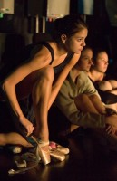 A teenage dancer puts on her pointe shoe as she watches from the side.