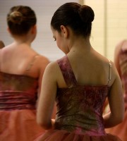 Ballet students in rust-colored costumes wait in the studio