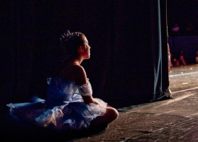 A young ballerina in purple tutu sits watching from the wings.