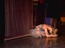 A dancer in mauve rests her head on the stage floor as she stretches forward over crossed legs.